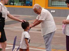 Intergeneracional. Una anciana para por la calle a un niño que camina con su madre para preguntarle si es un buen estudiante y un niño bueno y obediente con su madre.