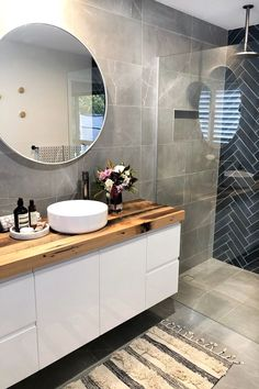 Looking for bathroom inspo that's anything but boring? This navy blue and charcoal bathroom with herringbone tile feature wall is sure to inspire!