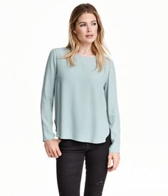 Long-sleeved blouse in woven crêpe fabric. Opening and button at back of neck. Rounded hem.