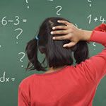 Learning dusabilities frequently associated with ADD. Young femaile student having difficulty with math problem on chalkboard displaying symptoms of Dyscalculia.