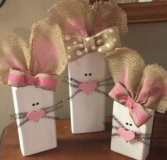 "How adorable would these cute wooden Easter bunnies look with the rest of your spring decorations! Display these on your mantle, table or as part of a centerpiece!  Each bunny has burlap ears with a ribbon bow, black wire whiskers and a pink heart nose! Set of 3. Each bunny is made from 2x4 wood with heights of 8, 10 and 12"" (not including ears). Insides of ears have been painted a light pink. Each wood block has been sanded, painted, lightly distressed then sealed with a protective co.."
