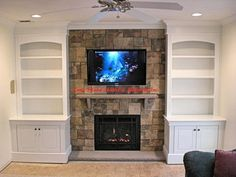 Long Island art and Millwork Hide the tv behind artwork over fireplace
