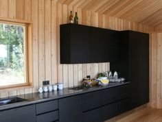 JOARC I ARCHITECTS • Holiday Villas • summerhouse kitchen, mökki, black and timber kitchen, timber walls