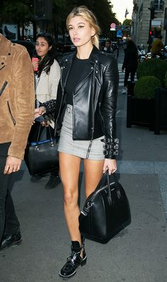 Hayley Baldwin wears a black top, plaid miniskirt, leather jacket, Balenciaga boots, and a Givenchy bag