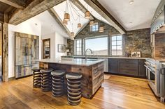 """""""The combination of so many different elements—metal, stone, barn wood, quartzite, painted cabinets, and stainless steel—all come together beautifully,"""" said the owner of this Vermont home."""