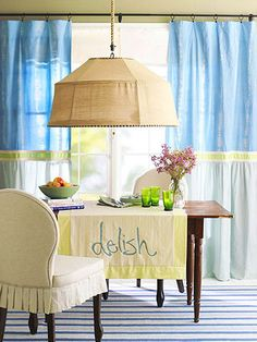 A basic flat sheet transforms this dining space from drab to delectable. We fashioned the curtains from four sheet parts, stitching the tie-dyed tops to lightly colored bottoms and embellishing the seams with ribbon.  The runner is a sheet too.