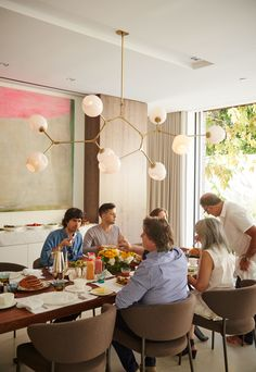 Dining Room and Chair In the dining room, family and friends come together over a walnut-slab dining table from BDDW. The dining chairs are from Minotti, and the Branching Bubble chandelier is by Lindsey Adelman.