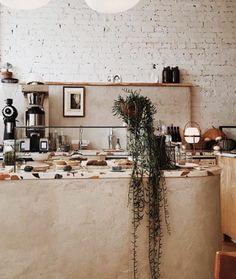 terrazzo countertops inside modern interior of cafe coffee shop in hamilton, canada called synonym. #counter #countertops #terrazzo #succulent #indoorplant #greenery #clay #coffeeshop #cafe #canada #interiordesign #paintedbrick #brickwall