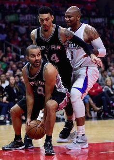 Danny Green Photos - Tony Parker #9 of the San Antonio Spurs grabs the rebound in front of teammate Danny Green #14 and Marreese Speights #5 of the Los Angeles Clippers during the game at Staples Center on December 22, 2016 in Los Angeles, California. - San Antonio Spurs v Los Angeles Clippers