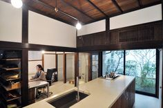 事務所スペースで作業をする相原さん。以前入っていた壁を取り払い、DK、事務所スペースとバスをつなげて一体化し、気持ちの良い広がりのある空間にした。