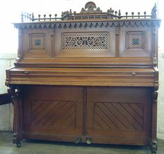 A Seiler XB upright piano with a Gothic style french polished sycamore case at Besbrode Pianos.