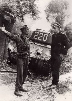 """SS-Sturmbannführer Erwin Meierdress (right), commander of 1./SS-Panzerregiment 3 of the Totenkopf Division, who took part in the battles east of Warsaw, where his unit destroyed many Soviet tanks and SPGs. He was killed in Hungary on 4 January 1945. The SS-Hauptsturmführer on the left is wearing the M44 camouflage drill uniform in the """"Dot"""" pattern. Behind them is a knocked out T-34/85. Photo taken in August 1944."""