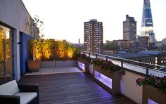 Bermondsey #roof #terrace with view of #Shard at night time :: LED lit custom designed planters, Silver birch and low strawberry trees on a hardwood and sandstone deck.