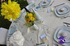 Mesa para bautizo, con pompones, recuerdos y botellas de vidrio como floreros