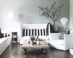 A repurposed cart sits central to the convergent grey scale. A hand painted tree seemingly grows up the wall adding to the organic creativity of the space. Black stripes present on scattered throw pillows deconstruct the stark white of the sofas, while the soft textures and comfortable shape of the sofa balances the stripped down palette.