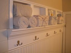 What a great idea ~ using stud space for storage with towel hooks below!     Beautiful Storage Space ~ Bathroom Walls