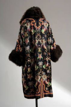 1990.390 (rear view) Coat of black satin embroidered with multicolored chinoiserie pattern and ribbons. Wide sable collar. Fingertip-length sleeves with sable trim. Falls below the knee. Black and blue velvet lining. Chicago History Museum