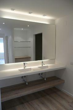 Encimera de solid surface con picas integradas suspendida en baño principal con estante ingletado realizado con el mismo parquet de la vivienda by SMSTUDIO
