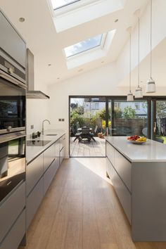 A modern side kitchen extension with large feature sliding doors onto a rear timber decking Best Modern Kitchen Lighting Ideas and Tips design with island Small Kitchen Lighting Ideas Pictures for Low Ceilings - HARP POST Open Plan Kitchen Living Room, New Kitchen, Kitchen Decor, Kitchen Lamps, Kitchen Ideas, Kitchen Cabinets, Kitchen Time, Grey Cupboards, Kitchen Wood