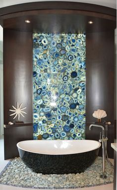 nautical accessories; Stunning bathroom design with a backlit blue geo  wall and lovely nautical accessories featuring a stone casted sunflower starfish and a clamshell on a stand; nautical decor ideas; coastal living inspiration