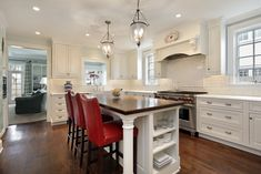 White kitchen with white ceiling, walls and cabinets.  Long custom kitchen island with red stools sits in the center of the large kitchen