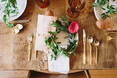 Gold flatware, wood table, greenery