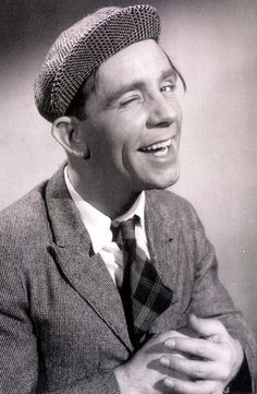Norman Wisdom wearing his familiar turned up flat cap.  A comic genius with a pliable sad face and mastery of falling over his own feet, he also had a fine singing voice and appeared in several movies - often as a naïve simpleton who is tricked but through honest endeavour wins out over all obstacles