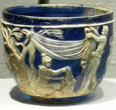This first century Roman Glass Cup with raised figures was once owned by J.P. Morgan and is called the Morgan Cup. It is a cameo with two layers: opaque white over translucent deep blue. The cup was blown and cased, then ground, carved, and polished.
