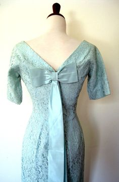 Nice touch with the large satin bow with lengthy legs that decorates the back of this pale blue lace dress from the1950s.