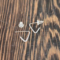 "- 925 Sterling Silver  - Post style hoop  -Mini triangle hoop earrings  - 1/2 inch x 1/2 inch    Minimalist geometric earring tiny and lightweight, easy to wear all day    These earrings are hand formed and hammered from 925 sterling silver wire and feature a post earwire with a silicone earnut that holds comfortably and securely.  The bottom point of these petite hoops hang just below your earlobe and are easy to wear all day. The total length is 1/2"" and the width is 1/2"" at it's widest…"