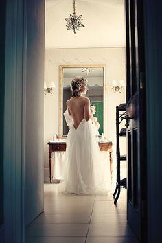 Stunning bride slips on her Amanda Caroline Couture dress. Photography by www.dottiephotography.co.uk