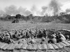 U.S. troops of the 1st Battalion, 18th Infantry Regiment, 1st Division, deep in War Zone C, crouch in a sandbagged mortar position as smoke rises from B-52 strikes against suspected Viet Cong positions along the Cambodian border during Operation Attleboro, November 20, 1966.