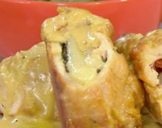 Abrir las pechugas cual si fueran un libro, rellenar con rúcula, queso y morrón asado. Salpimentar las pehugas. Cerar con palillos. Dorar en oliva de ambos lados. Una vez doradas, untar con mostaza y terminar de cocer al horno con base de oliva por unos 10 minutos.  Para las papas, cocerlas con piel y sal al horno con base de oliva. Aplastarlas. Dorar con manteca y romero en sartén y terminar con crema de leche, salpimentar.  Para la salsa, en la misma sartén que doramos el pollo, rehogar…
