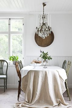 chateau chic #vintage #decor #interiors: Draped linen tablecloth, mounted baket on wall; Fine crystal chandelier.