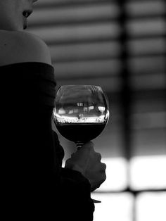 Woman holding a glass of red wine (Pinot wine glass shape with large bowl)