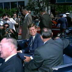 """1962. 23 Mars. By Robert KNUDSEN. KN-C20707. President John F. Kennedy sits in a convertible with Governor of California, Edmund G. """"Pat"""" Brown (right, back to camera), following President Kennedy's arrival at Alameda Naval Air Station in Alameda, California. University of California regent, Edwin W. Pauley, sits in jump seat (left, foreground). White House Secret Service agents, Roy Kellerman (left) and Gerald A. """"Jerry"""" Behn (right), stand behind car"""