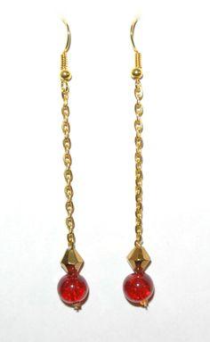 Boucles d'oreilles en chaine dorée avec une perle dorée et une ronde rouge.