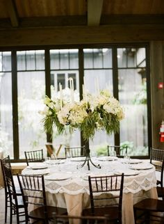 Beige table clothes with white lace overlay. Thin black sconces hold the flower and candle centepieces
