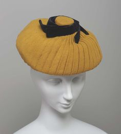 """Hat of mustard wool jersey, pleated into knob on top; knob trimmed with stiffened bands of black velvet. Label: """"Nellie Louise New York"""""""