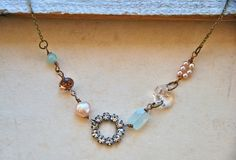 This is an antique brass chain.  It features a glass rhinestone circle,freshwater pearl,tiny pink glass pearls,a semi-precious light blue amazonite bead,a vintage glass chandelier prism and a sea blue quartz gemstone. . The necklace closes with a lobster claw. The necklace finishes with a lobster claw closure. This is such a pretty and romantic necklace