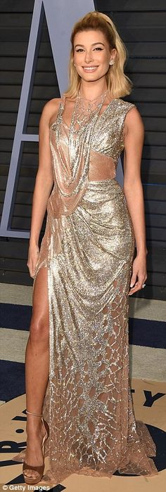 Golden girl: The runway queen, 21, poured her incredible figure into an glittering chain-m... #haileybaldwin