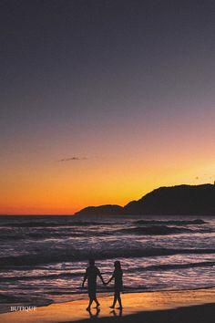 Um lindo por do sol de caminhada na praia para uma sessão de fotos pré casamento