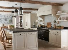 With rough, reclaimed beams overhead, rugged limestone tiles underfoot, and the aroma of fresh-baked bread wafting from the French-made La Cornue oven, the kitchen in this remodeled home in Westport, Connecticut, is irresistible. - Photo: Michael Partenio / Design: Anne-Marie Barton