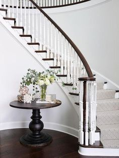Elegant foyer features a curved staircase a stained handrail and white spindles as well as a gray diamond pattern stair runner lining the steps. Foyer boasts a distressed black round foyer table lining the curved staircase wall. Foyer Staircase, White Staircase, Staircase Runner, Staircase Remodel, Curved Staircase, Entrance Foyer, Staircase Design, Stair Runners, Entrance Table