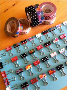 washi binder clips!  probably best with white or colored clips if the tape is sheer.
