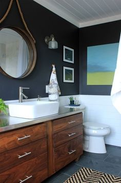 Love this nautical style bathroom, especially the contrast between the clean white tiles and the dark navy toned wall. And look at that unique mirror, gorgeous!
