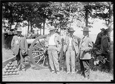 Union and Confederate soldiers gather around a cannon. Gettysburg 1913
