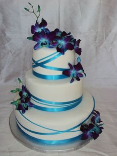 """Another pinner said: """"Jenna's Orchids- Blue dendrobium orchids atop a fondant covered cake wrapped with teal ribbons of varying widths."""" I would want different flowers, but I love this cake. Blue Orchid Wedding, Peacock Wedding Cake, Purple Wedding Cakes, Beautiful Wedding Cakes, Beautiful Cakes, Wedding Colors, Wedding Flowers, Blue Wedding Centerpieces, Blue Dendrobium Orchids"""