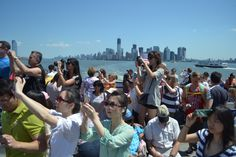 Tourists on their way to Statue of Liberty with Manhattan in the back