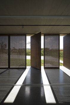 Perforated doors create a picture due to the incidence of natural lighting on the floor.